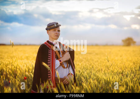 Man in the sunset field. He is wearing traditional Eastern Europe folk costumes. - Stock Photo