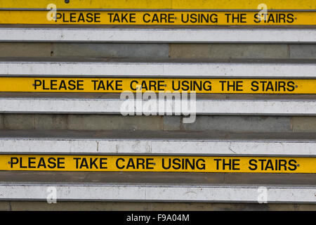 Please take care using the Stairs yellow information signs on steps - Stock Photo
