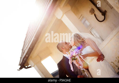 Happy bride and groom posing by the old house - Stock Photo