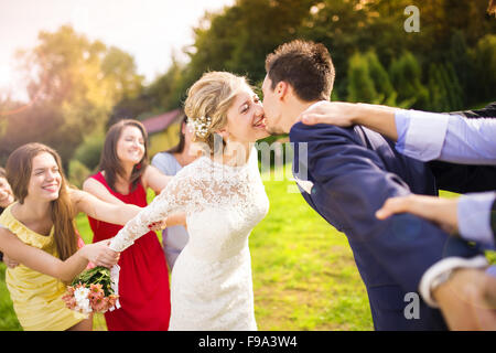 Funny portrait of newlywed couple kissing, bridesmaids and groomsmen pulling them away in green sunny park - Stock Photo