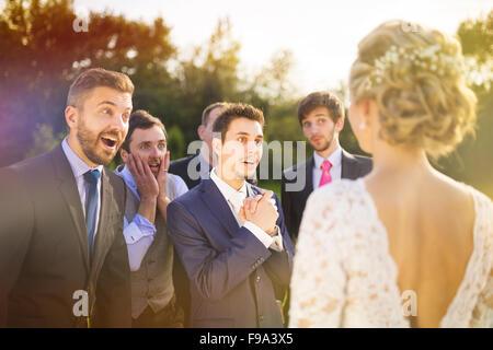 Portrait of surprised groomsmen looking at beautiful bride outside - Stock Photo