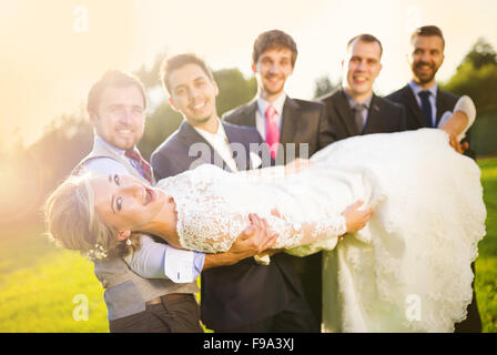 Outdoor portrait of young groom with his friends holding beautiful bride - Stock Photo
