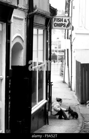 Girl and dog waiting outside fish and chip shop, Whitby, North Yorkshire - Stock Photo