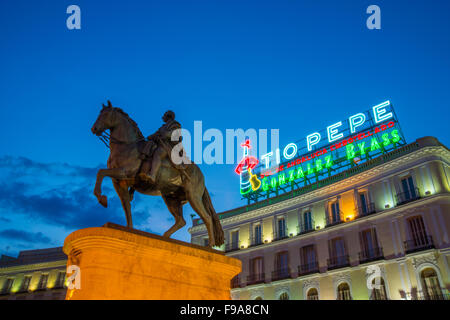 Tio Pepe neon sign on its new location and Carlos III statue, night view. Puerta del Sol, Madrid, Spain. - Stock Photo