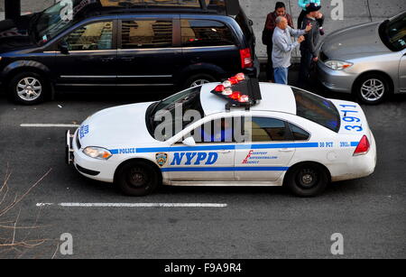 New York City:  NYPD police car with flashing red and white lights on Broadway at West 143rd Street in Harlem - Stock Photo