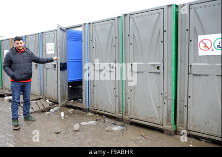 A refugee from Afganistan stands with a row of dirty Portaloo toilets in the Jungle refugee camp in Calais on a - Stock Photo