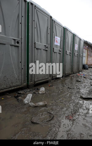 Row of dirty Portaloo toilets in the Jungle refugee camp in Calais sit in the mud on a rainy winter morning. © Becky - Stock Photo