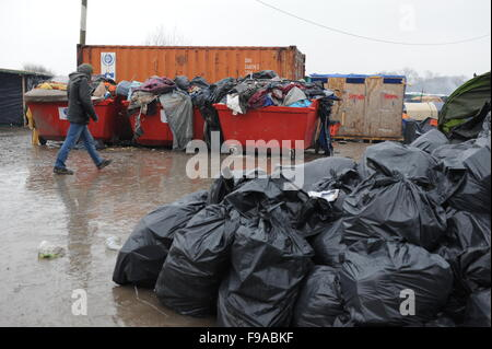Overflowing skips of rubbish and black bin bags of rubbish in the Jungle refugee camp, Calais on a wet rainy winters - Stock Photo