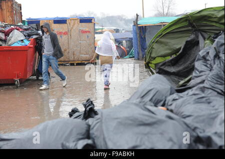 Row of dirty temporary showers and portaloo toilets in the Jungle refugee camp in Refugees run through the rain - Stock Photo