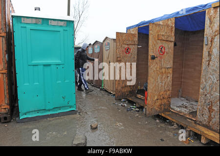 Row of dirty temporary showers and portaloo toilets in the Jungle refugee camp in Calais on a rainy muddy winter - Stock Photo