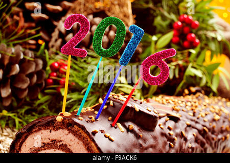 a yule log cake, traditional of christmas time, topped with glittering numbers of different colors forming the number - Stock Photo