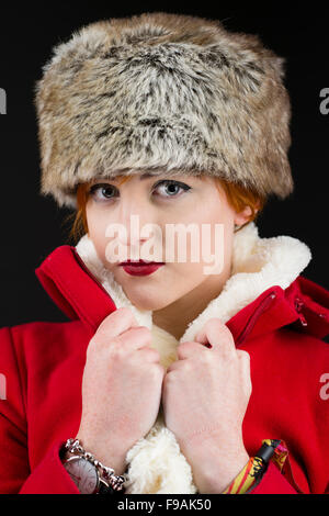 Winter fashion and clothing: A single solo young teenage woman girl with flame red short hair by herself, wearing - Stock Photo