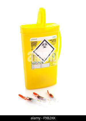 Yellow medical sharps disposal box with three hypodermics on a White Background - Stock Photo