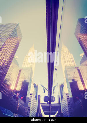 Vintage style Manhattan skyscrapers reflected in windows, NYC, USA. - Stock Photo