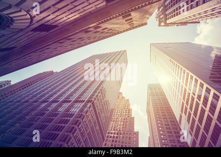 Vintage stylized photo of skyscrapers in Manhattan at sunset, New York City, USA. - Stock Photo