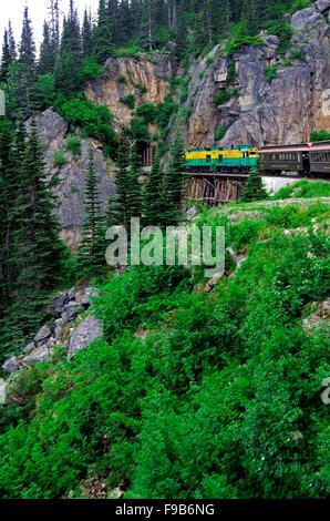 White Pass Railroad electric engine pulls train passenger cars over trestle bridge towards tunnel in the rocks. - Stock Photo