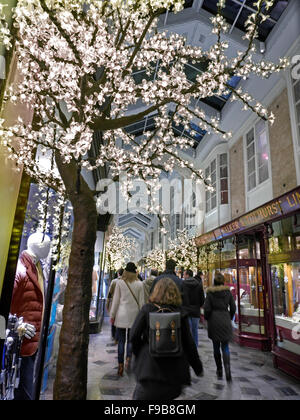 Busy Burlington Arcade in Piccadilly with traditional Christmas decorations and shoppers with shopping bags London - Stock Photo
