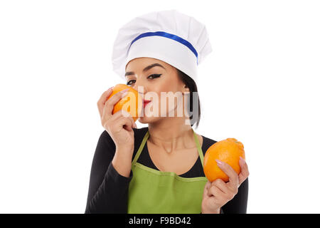 Beautiful young woman cook holding and sniffing oranges - Stock Photo