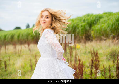Happy Bride: A young blonde haired woman wearing a lacy white wedding dress outdoors in a field on an autumn afternoon, - Stock Photo
