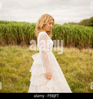 A side profile of a young blonde haired woman wearing a lacy white wedding dress outdoors in a field on an autumn - Stock Photo