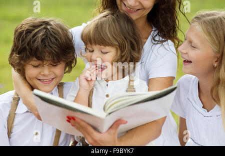 Mother is seating and reading a book to her children in the green park - Stock Photo