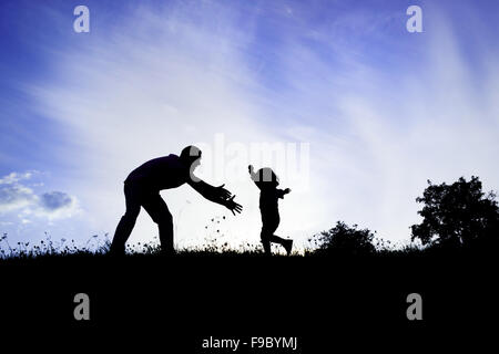 Silhouette of happy father having fun with his son - Stock Photo