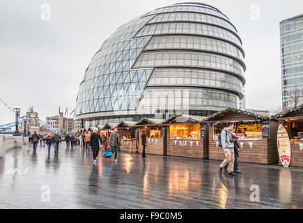 London Bridge City Christmas Market, Southwark, London SE1, on a wet day with City Hall in the background - Stock Photo
