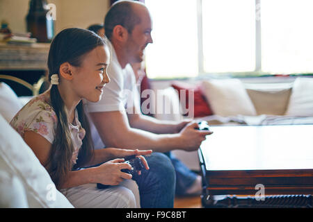 Smiling girl playing video games with her father - Stock Photo