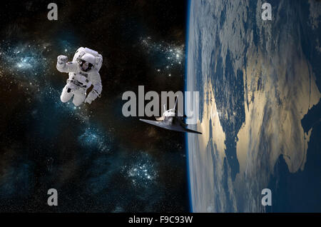 An astronaut drifting in space is rescued by a space shuttle orbiting Earth. - Stock Photo