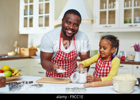 African-American man and his daughter in aprons cooking homemade pastry - Stock Photo