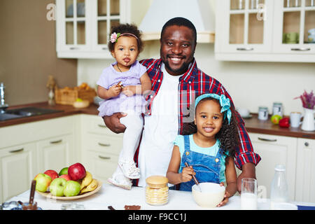 Happy African-American family looking at camera in the kitchen - Stock Photo