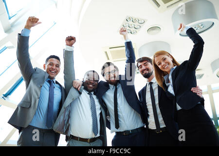 Business team with arms raised and smiling - Stock Photo