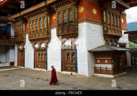 Buddhist monk striding through the courtyard of the monastery and fortress Punakha Dzong, Punakah, Bhutan - Stock Photo