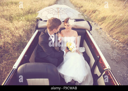 Bride and groom in a vintage car - Stock Photo