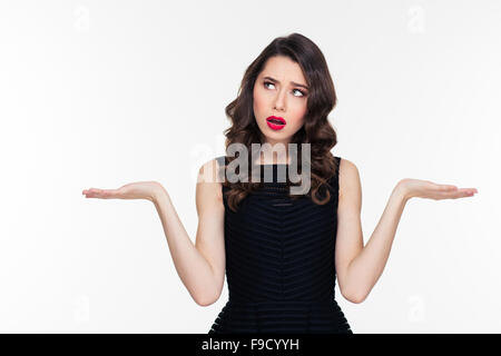 Confused thoughtful curly young woman with retro hairstyle and red lips holding copyspace on both palms over white - Stock Photo