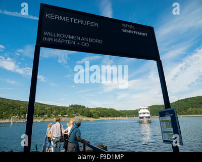 Tourists on the banks of the Rursee lake wait for the arrival of a passenger ship in the German Eifel National Park. - Stock Photo