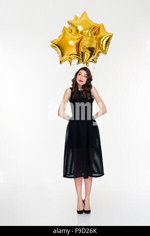 Full length of shy cute beautiful curly young female in retro style hiding star shaped balloons behind herself - Stock Photo