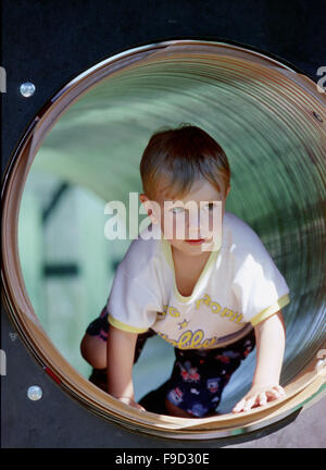 Little Boy Crawling in Pipe on The Playground - Stock Photo