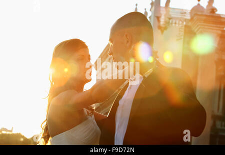 Beautiful wedding with bride and groom couple kissing in the sun - Stock Photo