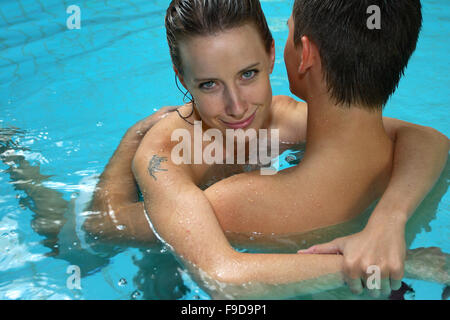 Hugging Couple in Swimming Pool - Stock Photo