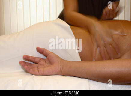 Hands Massaging Man's Back - Stock Photo
