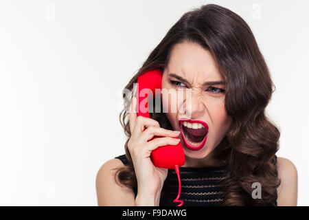 Close up of angry mad curly young woman in retro style screaming and talking on telephone over white background - Stock Photo