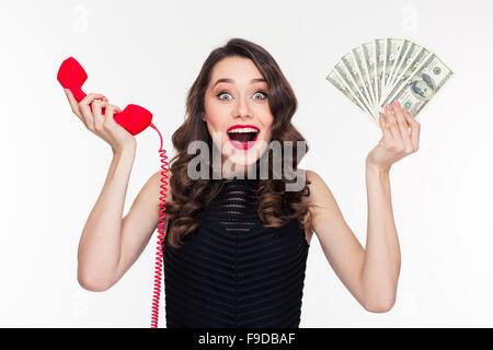 Beautiful excited happy young woman in retro style holding money and telephone receiver over white background - Stock Photo