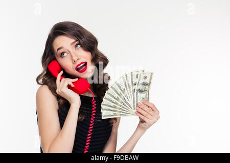Attractive joyful curly young female with bright makeup in retro style holding money and talking on telephone - Stock Photo