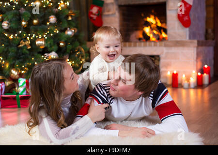 Happy young parents and child have a fun near Christmas tree at home.  Father, mother and son celebrating New Year - Stock Photo
