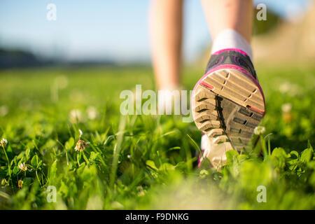 Closeup runner feet running outdoors on the green grass. - Stock Photo
