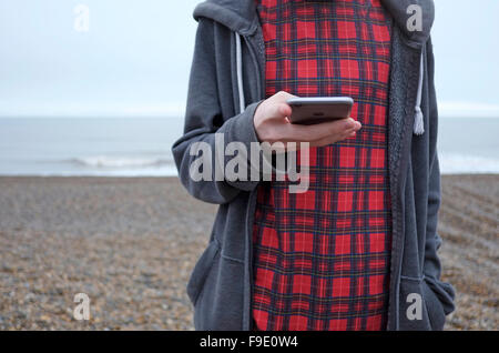 young male teenager man using mobile phone on beach, weybourne, north norfolk, england - Stock Photo