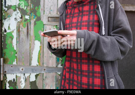 young male teenager man using mobile phone - Stock Photo