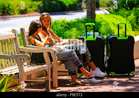 Two college aged girls sitting on a street bench in downtown Santa Barbara with the suitcases waiting for the bus. - Stock Photo