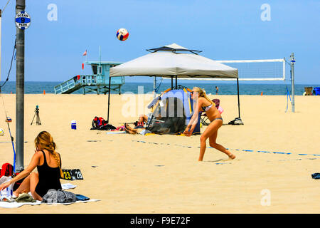 Young college girls playing beach volleyball on Santa Monica beach in California - Stock Photo